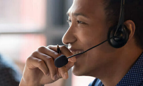Smiling young african businessman call center agent wear wireless headset laugh at workplace, cheerful happy black male telemarketer operator have fun at work break in customer service support office
