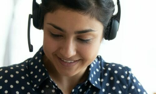 Happy indian girl student wear headset study online with webcam teacher write notes, happy young woman listen lecture watch webinar on laptop sit at desk, distance e learn language education concept