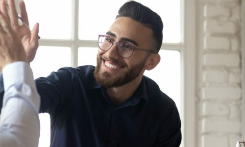 Excited millennial Arabic businessman give high five to Caucasian male colleagues at meeting, smiling multiethnic businesspeople join hands celebrate business success in office, cooperation concept